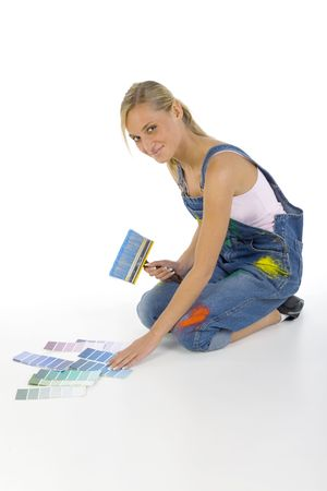dungarees: Young smiling blonde wearing dungarees with paintbrush in hand. Sitting on floor nearby color palettes. Looking at camera. Whole body, white background Stock Photo