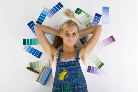 Young smiling blonde wearing dungarees. Lying on floor among color palettes and paintbrush. Looking at camera