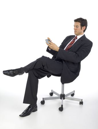 arms chair: Focused, handsome businessman. Seating on chair with palmtop in hands. White background