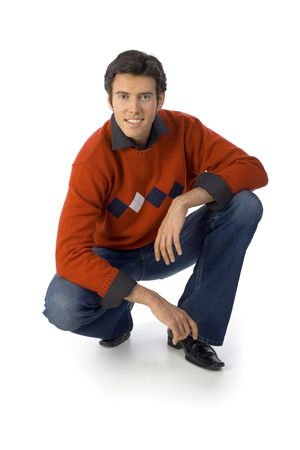 denim jeans: Smiling, handsome man wearing orange jersey, black shirt and denim jeans. Crouching, looking at camera. Isolated on white in studio