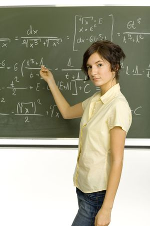 Teenage girl standing in classroom. Showing exercise on blackboard. Looking at camera. Side view Stock Photo