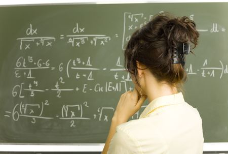 Teenage girl standing in classroom. Looking at blackboard and wondering about something. Rear view