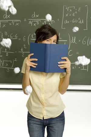 Teenage girl standing in classroom, in front of blackboard. Hiding behind  book. Someone throwing pieces of paper into her. Front view