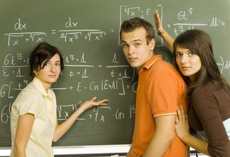 Small group of teenagers standing in front of blackboard. Trying to understand exercise on blackboard. Looking at camera, side view