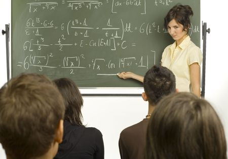 Small group of teenagers sitting in front of blackboard. One girl standing  beside the blackboard and showing something to the rest Stock Photo - 968881