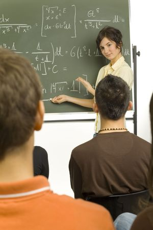 Small group of teenagers sitting in front of blackboard. One girl standing  beside the blackboard and showing something to the rest Stock Photo
