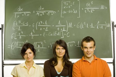 Small group of teenagers sitting in front of blackboard. Two girls and one boy. Looking at camera, front view