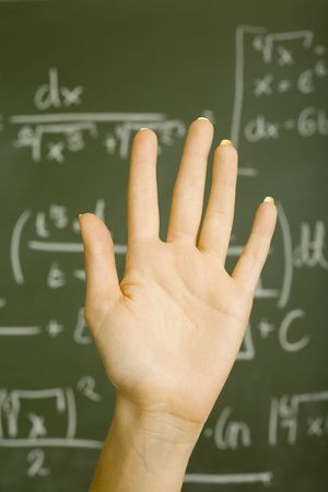 Raised hand of teenage girl in front of blackboard