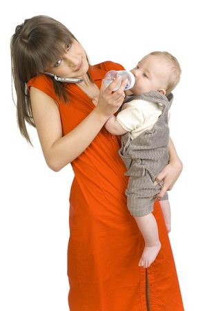Young mother with baby boy on hand. Feeding baby and talking by mobile phone. Looking at camera. Isolated on white