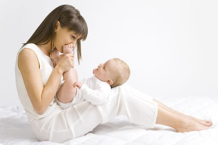 tissu blanc: Jeune m�re avec le gar�on de b�b�. Se reposer sur le tissu blanc et avoir lamusement. Bodys entiers, vue de c�t�