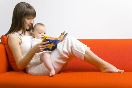 Young mother hugging baby boy. Sitting on orange couch. Reading to him book. Whole bodys. Side view Stock Photo