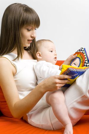 Young mother hugging baby boy. Sitting on orange couch. Reading to him book. Side view