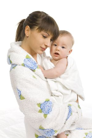 Young mother in bathrobe hugging baby boy in towel. White background. Side view
