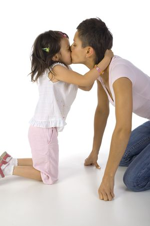 Mother with daughter kissing and kneeling on the floor. White backgriund, side view