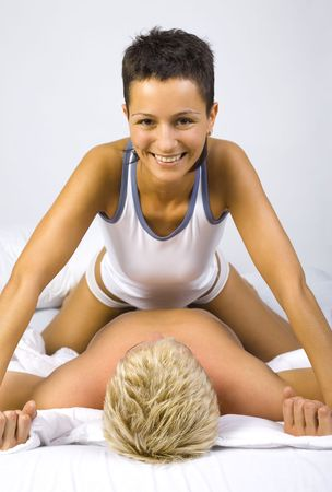 superiority: Young, smiling woman sitting on man in bed, showing her domination. Gray background, front view Stock Photo