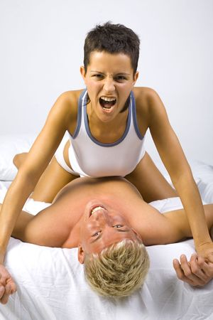 superiority: Young, screaming woman sitting on man in bed, showing her domination. Gray background, front view