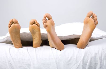 foots: Foots of young couple lying in bed. Gray background, front view