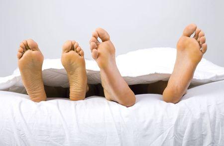 Klauenöl der jungen Paar im Bett liegend. Grauer Hintergrund, der Ansicht von vorn  Standard-Bild