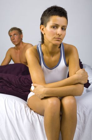 unsatisfied: Young sad woman sitting on bed, nearby unsatisfied man. Woman looking at camera. Gray background, front view
