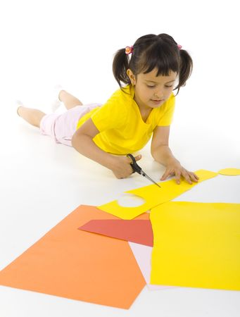 Little girl lying on the floor. Cutting paper with scissors. White background photo