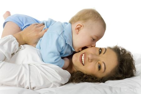 bit: Young happy mother hugging baby. Woman is lying in bed and looking at camera. Baby is lying on her, trying to bite. White background  Stock Photo