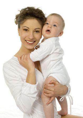 madre e hijo: Young feliz madre abrazando beb�. La mujer est� sentada en la cama y mirando a c�mara, beb� est� sentado en su brazo. Fondo blanco
