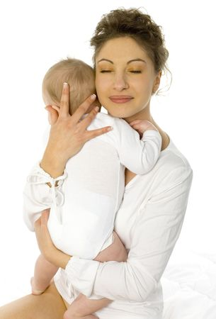 Young mother is sitting in bed with baby. Hugging baby with closed eyes. White background Stock Photo - 1105802