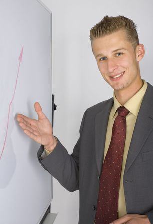 Young businessman standing in front of the blackboard. Smiling and showing the graph. Looking at camera, gray background photo