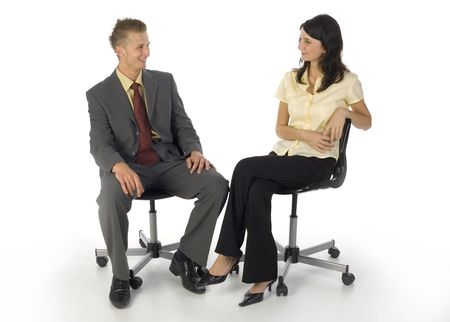 instruct: Young businessman and businesswoman sitting on chairs. Lookig at each others and smiling. White background