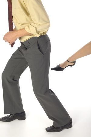 Womans leg want to kick a businessman. White background