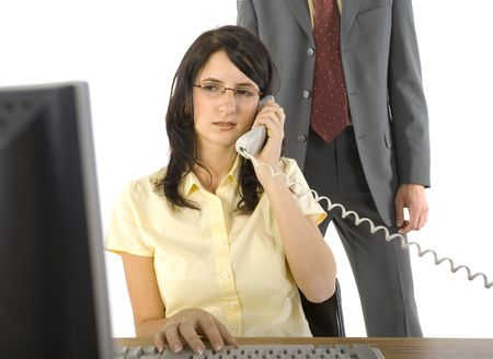 molest: Young businesswoman sitting at desk, talking on phone. Working on computer. Man in suit standing behind her. White background