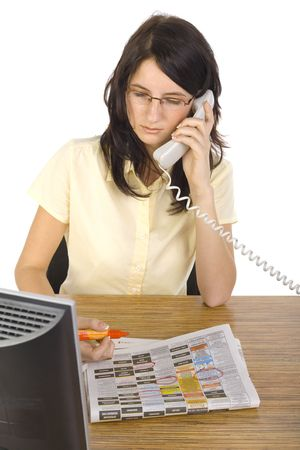 Young beauty businesswoman sitting at desk, talking on telephone and marking something in newspaper. White background, front view Stock Photo - 1105857