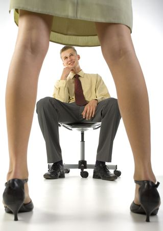 Young, smiling businessman, sitting on chair in front of woman in skirt. White background