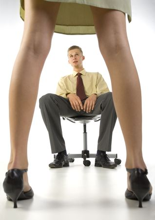 molestation: Young, scared businessman, sitting on chair in front of woman in skirt. White background