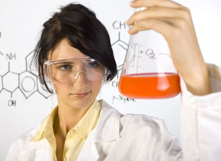 Young, beauty chemist girl in white apron. Holding beaker with orange liquid. Wearing goggles. Gray background Stock Photo - 1105866