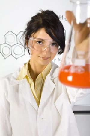 Young, beauty chemist girl in white apron. Holding beaker with orange liquid. Wearing goggles. Looking at camera. Gray background Stock Photo - 1105867