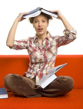 Young, confused woman sitting on orange couch. Holding a book on head. Looking at camera, white background photo