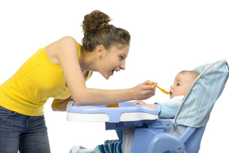 him: Young, beautiful woman with baby. Baby is sitting on babys chair. Mother is feeding him. White background, side view