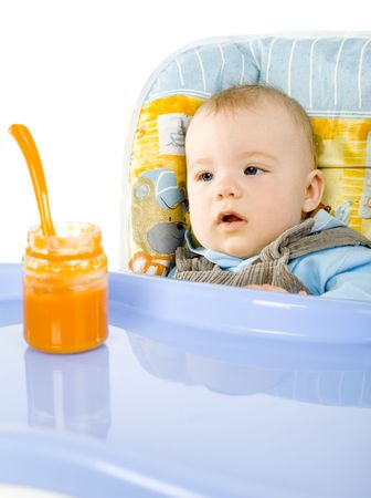 Pretty infant sitting on babys chair. Looking at orange pulp in jar. White background Stock Photo