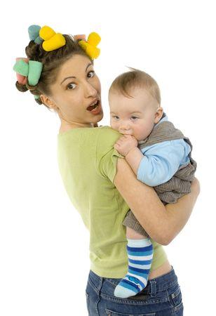 poco: Joven, bella mujer con el bebé en las manos. Bebé está mordiendo el brazo de la madre. Madre está mirando a cámara. Fondo blanco