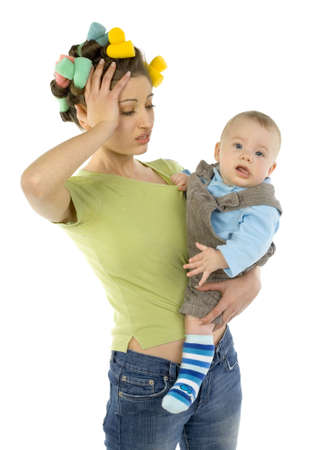 Young, depressed woman with baby on hands. Woman is holding hers head. Baby is looking at camera. White background, front view photo