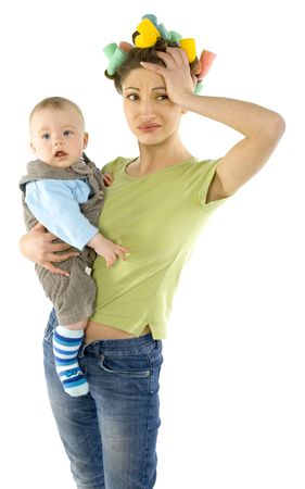 Young, depressed woman with baby on hands. Woman is holding hers head. White background, front view photo