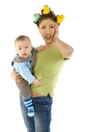 Young, depressed woman with baby on hands. Woman is looking at camera and holding hers head. White background, front view photo