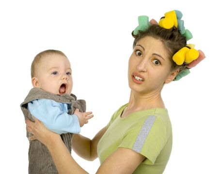 Young, depressed woman holding baby. Woman is looking at camera. Baby has opened mouth. White background, side view photo