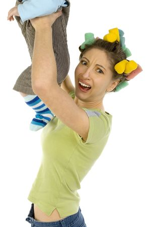 aversion: Young woman holding up  and smelling his nappy. Showing on her face aversion. Looking at camera, white background