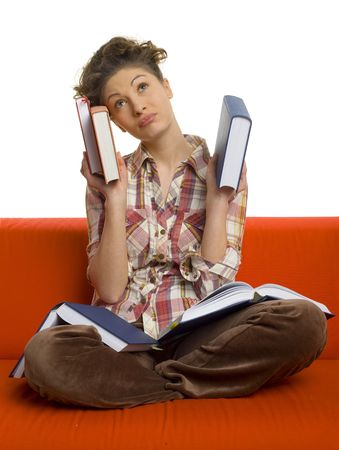 Young, confused woman sitting on orange couch. Holding books in hands. Looking up. White background photo