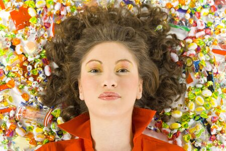 Young, beautiful woman lying on floor among candys. Smiling and looking at camera. Front view photo