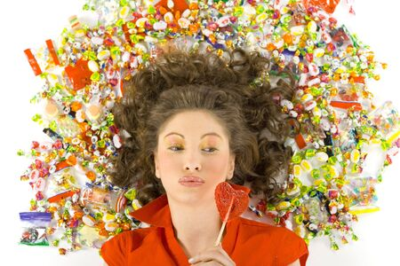 Young, beautiful woman lying on floor among candys with lollypop in hand. Looking at lollypop, front view. White background