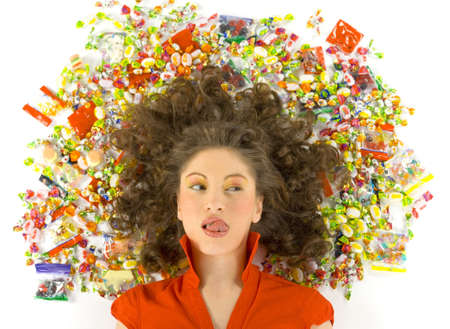 Young, beautiful woman lying on floor among candys. Looking at candys and licking her lips. Front view, white background Stock Photo