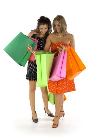 Two beautiful, young woman standing and holding bags. First woman is showing something in hers bag. Both woman are looking at bag. Isolated on white in studio. Whole body photo